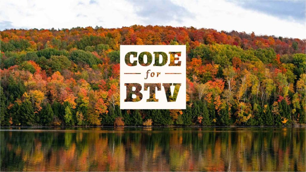 White square Code for BTV logo with transparent letters in front of trees with fall foliage.