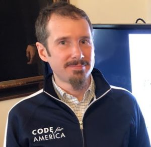 Picture of Brigade Captain Nick Floersch wearing a jacket that says 'Code for America'.